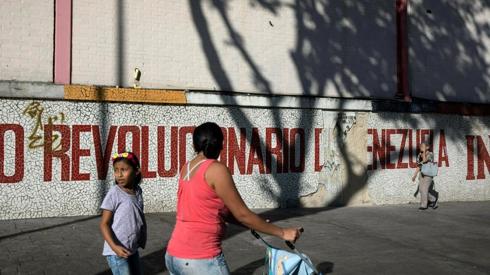 "People walk next to a mural that reads in Spanish ""Revolutionary of Venezuela"" in Caracas, Venezuela, Friday, Jan. 25, 2019. (AP Photo/Rodrigo Abd)"