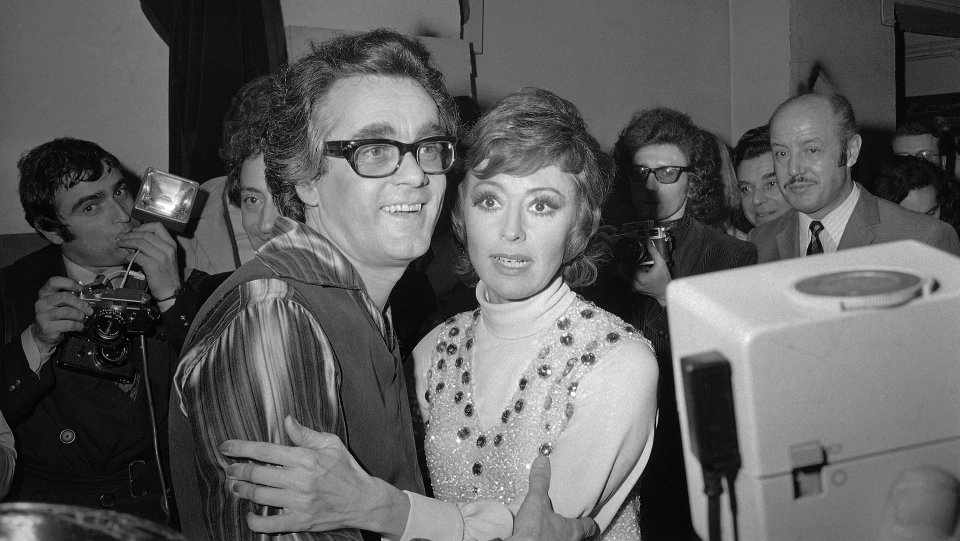 In this Jan. 20, 1972 file picture French-born Italian singer, dancer and actress Caterina Valente, right, embraces Franco-Armenian musical composer, arranger, conductor and pianist Michel Legrand after their show at the Olympia in Paris, France. (AP Photo/Michel Lipchitz, File)