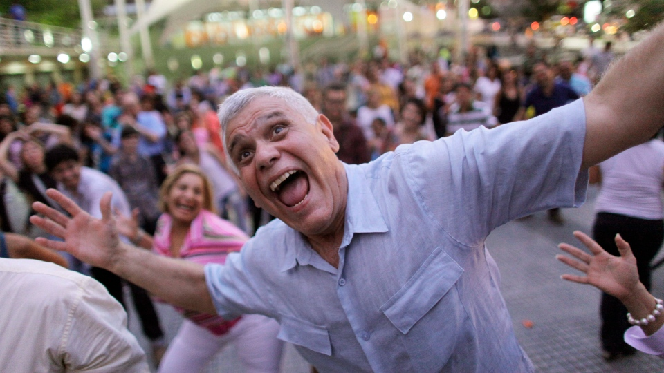 A man laughs during a session of laugher therapy in a public plaza in Caracas, Venezuela, Tuesday, July 9, 2013. (AP Photo/Ariana Cubillos)
