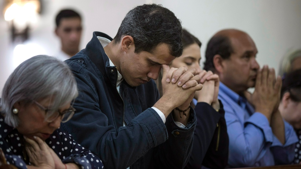 Opposition National Assembly President Juan Guaido, who declared himself interim president of Venezuela, prays next to his wife Fabiana Rosales, second from right, during Mass at a church in Caracas, Venezuela, Sunday, Jan. 27, 2019. (AP Photo/Rodrigo Abd)