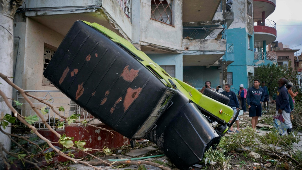 A truck is toppled against a home after a tornado in Havana, Cuba, Monday, Jan. 28, 2019. (AP Photo/Ramon Espinosa)