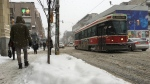 People navigate a snow-covered sidewalk on Queen Street in downtown Toronto Monday January 28, 2019. (Joshua Freeman /CP24)