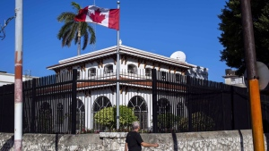 A 14th Canadian has fallen ill to an unexplained illness in Havana, Cuba, prompting further reductions in embassy staffing in the country. A man walks beside Canada's embassy in Havana, Cuba, Tuesday, April 17, 2018. THE CANADIAN PRESS/AP-Desmond Boylan