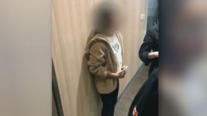 A 12-year-old girl who cannot be identified is made to stand against a wall and get measured by restaurant staff.