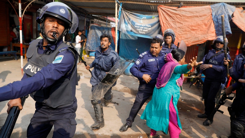 A Bangladeshi garment worker clashes with policemen during a protest in Savar, on the outskirts of Dhaka, Bangladesh, Wednesday, Jan. 9, 2019. (AP Photo)