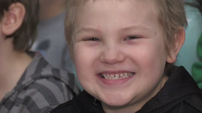 Dylan Roloson grins at an assembly held to honour him for saving his mom's life.
