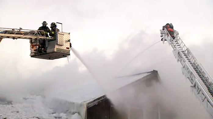 Ice and snow hang from the buckets of a fire truck where firefighters continue to battle a blaze at the Agincourt Recreation Centre in frigid February temperatures.