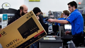 A cashier scans a television for a customer looks at Best Buy on Black Friday, in Ottawa on Friday, Nov. 25, 2016. THE CANADIAN PRESS/Justin Tang