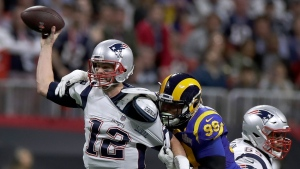 New England Patriots' Tom Brady (12) passes under pressure form Los Angeles Rams' Aaron Donald (99) during the first half of the NFL Super Bowl 53 football game Sunday, Feb. 3, 2019, in Atlanta. (AP Photo/Carolyn Kaster)