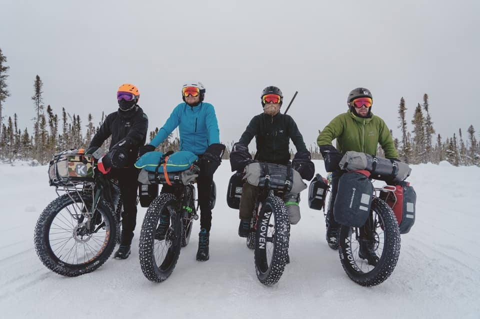 Four friends are fat biking through the north