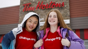 Mya Chau, left, 12, and Eve Helman, 12, who are digitally petitioning Tim Horton's to make the roll up the rim to win campaign more environmentally friendly, are seen outside a Tim Horton's in Calgary, Alta., Sunday, Feb. 3, 2019. (THE CANADIAN PRESS/Jeff McIntosh)