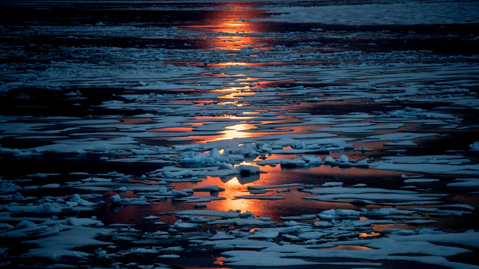 In this July 23, 2017, file photo the midnight sun shines across sea ice along the Northwest Passage in the Canadian Arctic Archipelago. (AP Photo/David Goldman, File)