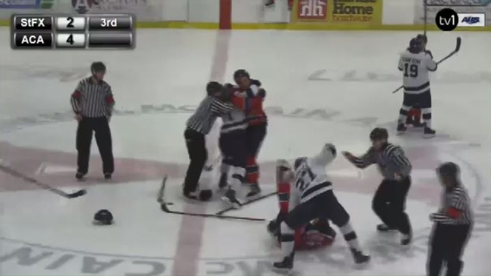 Sam Studnicka (27 in white) of the St. Francis Xavier X-Men punches Rodney Southam, a member of the Acadia Axemen, during a third-period brawl Saturday in Wolfville, N.S.