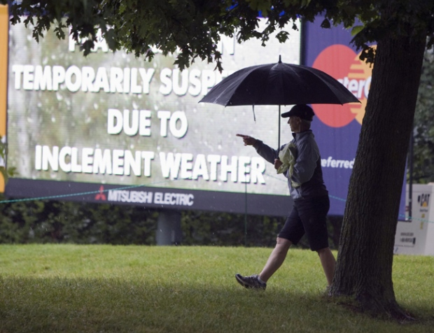 A spectator walks the course during a rain delay at the Canadian Open Golf championship in Oakville, Ont. on Thursday, July 23, 2009. (Frank Gunn / THE CANADIAN PRESS)