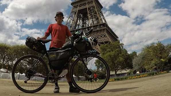 B'yauling Toni is seen standing in front of the Eiffel Tower during his cycling trip around the world. (B'yauling Toni/ Instagram)