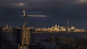 Condominiums are seen under construction in front of the skyline in Toronto, Ont., on Tuesday October 31, 2017. Home sales in Toronto and the surrounding area saw a small uptick in January, a sign that the real estate market in Canada's largest city remains stable. THE CANADIAN PRESS/Mark Blinch