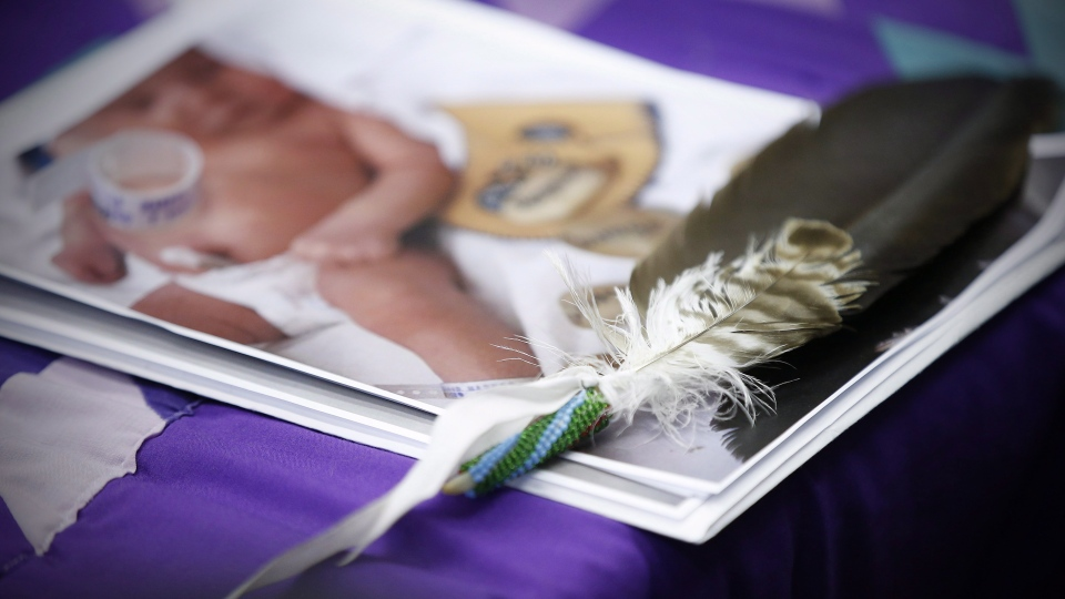 An eagle feather and a baby hospital ID bracelet sit on a photo of a newborn baby during a press conference in support of the mother who's newborn baby was seized from hospital by Manitoba's Child and Family Services (CFS) at First Nations Family Advocate Office in Winnipeg on Friday, January 11, 2019. THE CANADIAN PRESS/John Woods
