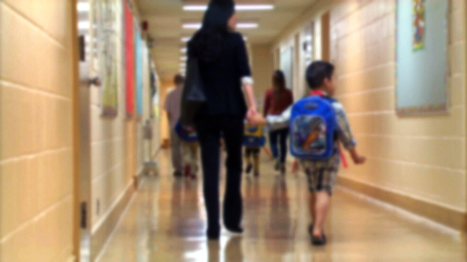 A child walks in the hallway of a school with a guardian in this undated photograph.
