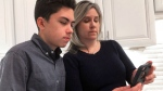 In this Jan. 31, 2019, file photo Grant Thompson and his mother, Michele, look at an iPhone in the family's kitchen in Tucson, Ariz., on Thursday, Jan. 31, 2019. Apple has released an iPhone update to fix a FaceTime flaw that allowed people to eavesdrop on others while using its group video chat feature. The repair is included in the latest version of Apple's iOS 12 system, which became available to install Thursday. Apple credited the Tucson teenager, Grant Thompson, for discovering the FaceTime bug. (AP Photo/Brian Skoloff, File)