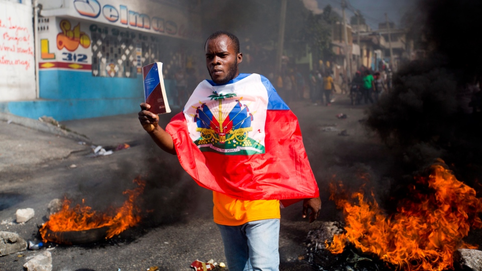 A demonstrator demands the resignation of President Jovenel Moise and demands to know how Petro Caribe funds have been used by the current and past administrations, in Port-au-Prince, Haiti, Thursday, Feb. 7, 2019.  (AP Photo/Dieu Nalio Chery)