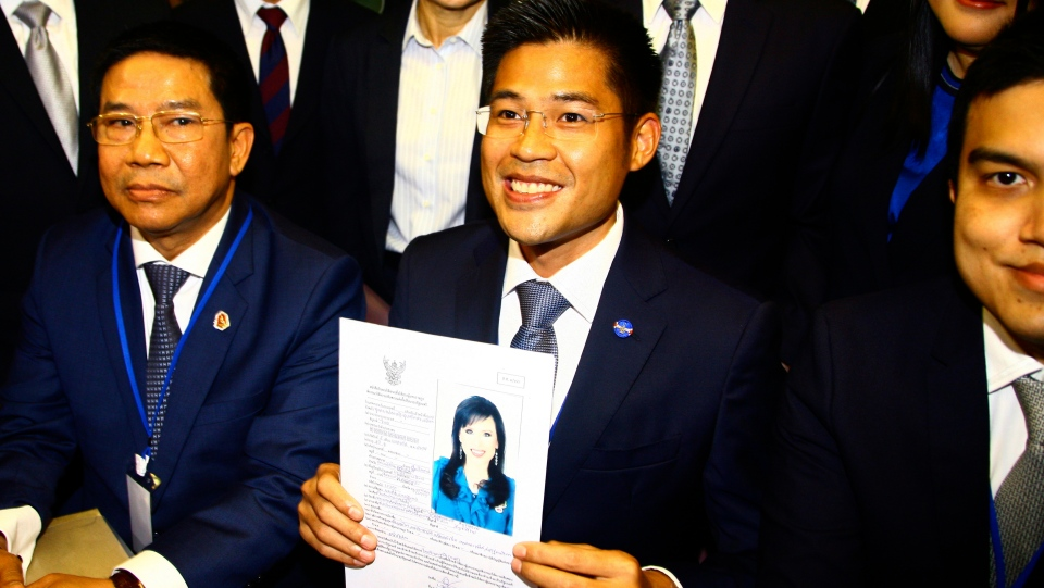 Leader of Thai Raksa Chart party Preecha Pholphongpanich, center, holds a picture of Princess Ubolratana at election commission of Thailand in Bangkok, Thailand, Friday, Feb. 8, 2019. The political party has selected the princess as its nominee to serve as the next prime minister. (AP Photo)