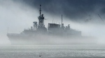 HMCS St. John's, one of Canada's Halifax-class frigates, heads through the fog as it returns to port in Halifax on Monday, July 23, 2018. THE CANADIAN PRESS/Andrew Vaughan