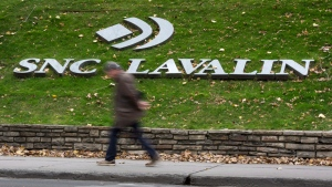 A man walks past the headquarters of SNC-Lavalin in Montreal on Nov. 6, 2014. (THE CANADIAN PRESS/Paul Chiasson)