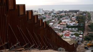 In this Jan 15, 2019 image, a section of newly-replaced border wall separates Tijuana, Mexico, above left, from San Diego, right, in San Diego. (AP Photo/Gregory Bull)