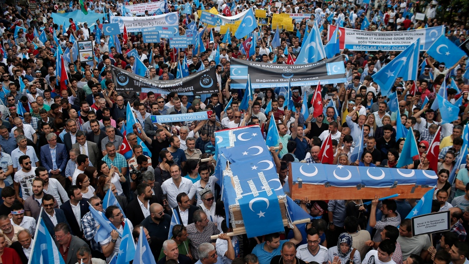 In this Saturday, July 4, 2015 file photo, Uighurs living in Turkey and their supporters, some carrying coffins representing Uighurs who died in China's far-western Xinjiang Uighur region, as they stage a protest in Istanbul, against what they call as oppression by Chinese government to Muslim Uighurs in the province.  (AP Photo/Emrah Gurel, File)