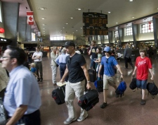 Passengers follow a VIA Rail employee to waiting buses at Central Station in Montreal, Friday, July 24, 2009. (Ryan Remiorz / THE CANADIAN PRESS)
