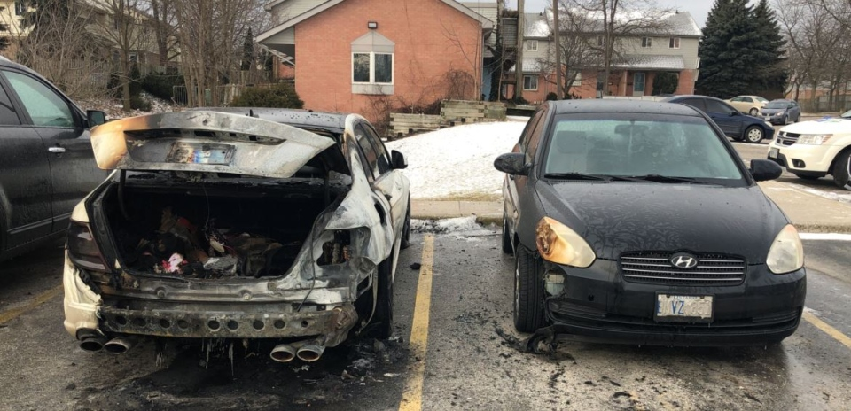 Another vehicle parked beside a burned Mercedes also has some damage.