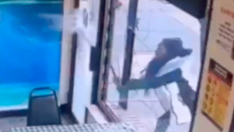 "In this Jan. 15, 2019 image taken from surveillance video, a woman smashes the windows of ""Back Home Restaurant"" in the Bronx borough of New York. Police say that she became upset after ordering a patty and was told that the restaurant had run out of them. She returned with a bat and smashed two windows. (New York City Police Department via AP)"