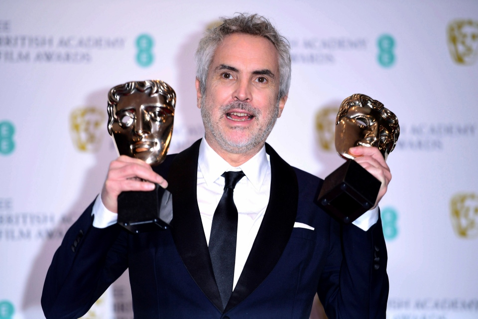 Alfonso Cuaron with his Best Film and Best Director poses for a photo in the press room at the 72nd British Academy Film Awards at the Grosvenor House Hotel in central London in Sunday, Feb. 10, 2019. (Ian West/PA via AP)