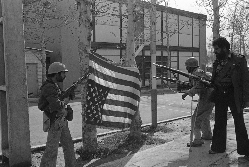 In this Feb. 12, 1979 file photo, Iranian rebels pose with a U.S. flag they bayonetted upside down on trees at Sultanabad Garrison northeast of Tehran, Iran. (AP Photo/Saris, File)