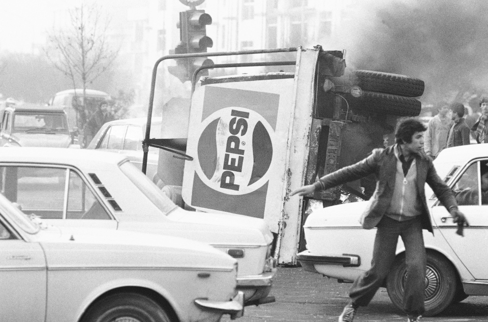 In this Dec. 27, 1978 file photo, an overturned truck with a Pepsi soft drink logo burns during riots in Tehran, Iran. (AP Photo, File)