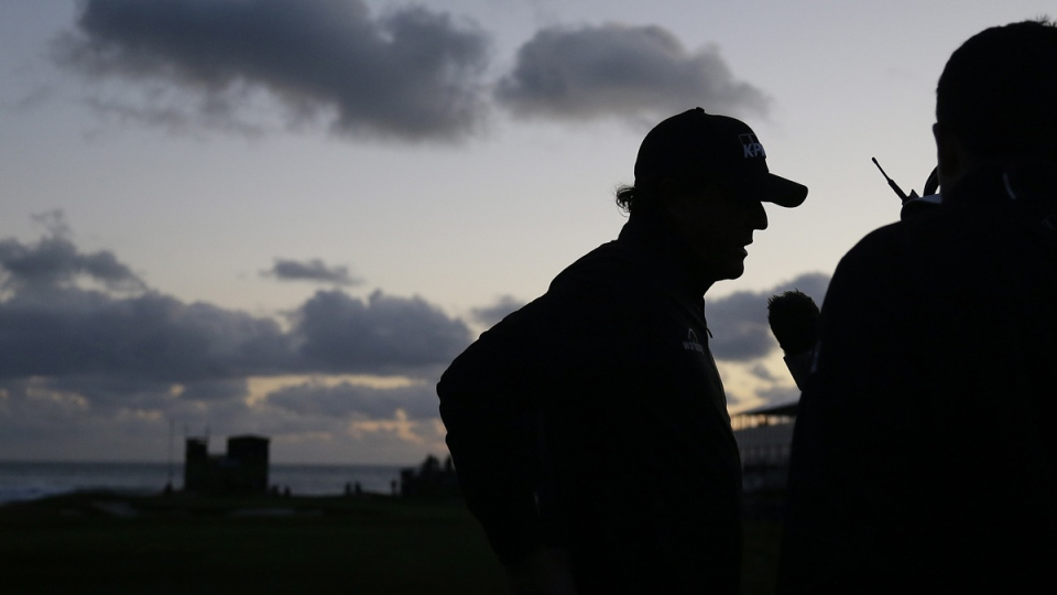 Phil Mickelson talks with reporters on the 17th green of the Pebble Beach Golf Links after play was stopped due to darkness, on Feb. 10, 2019. (Eric Risberg / AP)