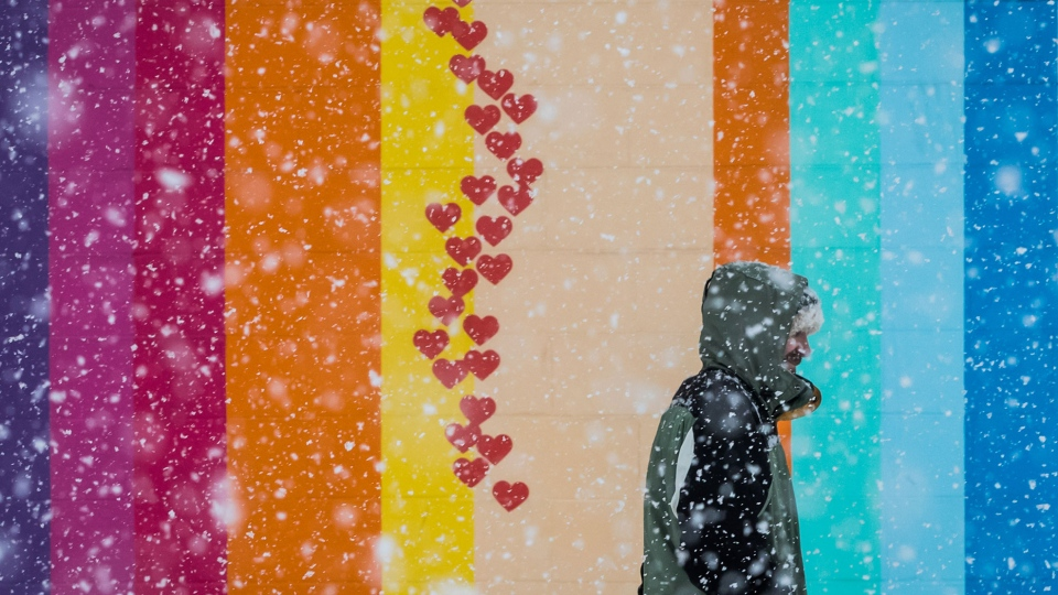 A man stands outside a brightly painted building as heavy snow falls in Vancouver, on Sunday Feb. 10, 2019. (Darryl Dyck / THE CANADIAN PRESS)