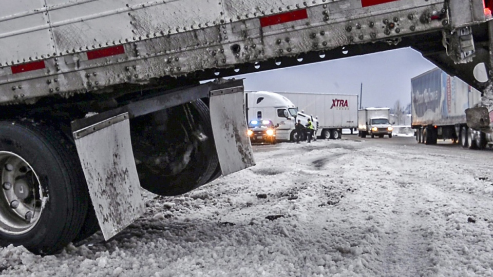 In this Saturday, Feb. 9, 2019, photo, state patrol troopers and drivers sort out the mess of a couple of semi-trailer trucks and a car that tangled in the heavy snow on the Fife curve of southbound Interstate 5. (Peter Haley / The News Tribune via AP)