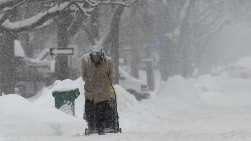 A man pulls his shopping cart along the snow-covered street in Ottawa on Wednesday, January 23, 2019. THE CANADIAN PRESS/Adrian Wyld