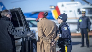 RCMP officers lead a suspect in a money laundering ring into a vehicle after he was arrested on Feb. 11, 2019 (Photo courtesy: RCMP)