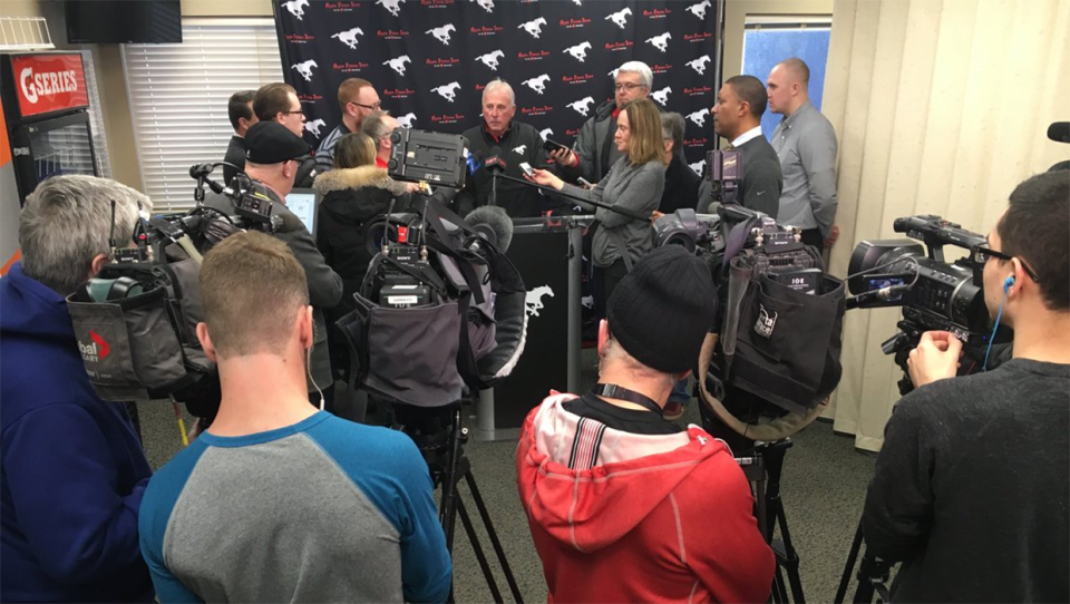 Stampeders' GM John Hufnagel is surrounded by reporters at a news conference in Calgary on Monday, February 11, 2019.