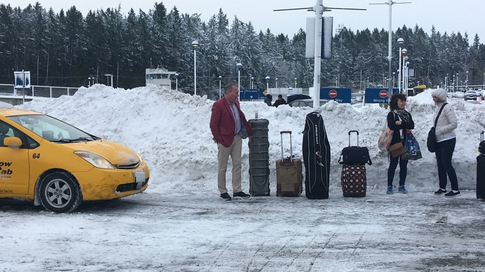 BC Ferries passengers wait in the snow for a cab at the Swartz Bay terminal near Victoria Monday, Feb. 11, 2019. (CTV Vancouver Island)
