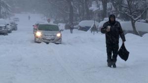 A man walks down a snow-covered street