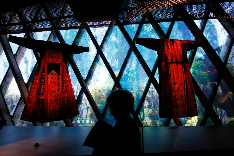 "In this Feb. 7, 2011 file photo, a woman views traditional Palestinian thobes during the exhibition ""Women in Orient"" at the Quai Branly Museum in Paris, France. The thobe, a brightly embroidered robe for women, has long been a staple of Palestinian life, sewn by village women and worn at weddings and parties. Now it'Äôs gaining prominence as a softer symbol of Palestinian nationalism, competing with the classic keffiyeh. (AP Photo/Christophe Ena, File)"