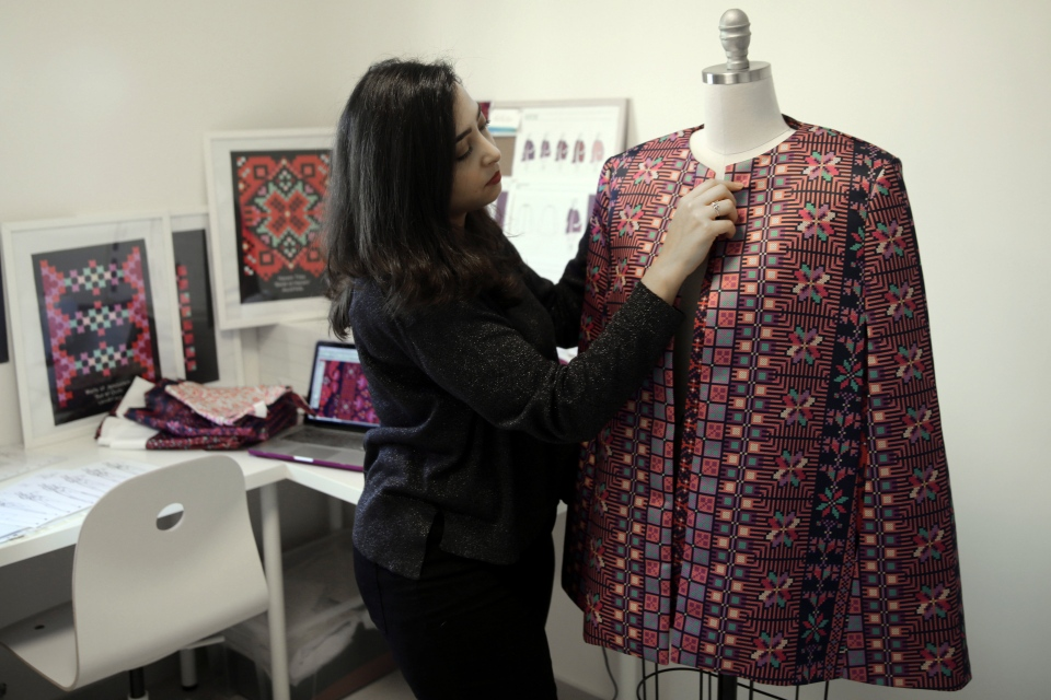 In this Tuesday, Jan. 29, 2019 photo, designer Natalie Tahhan works on a modern version of the traditional Palestinian thobe in her studio in east Jerusalem. (AP Photo/Mahmoud Illean)