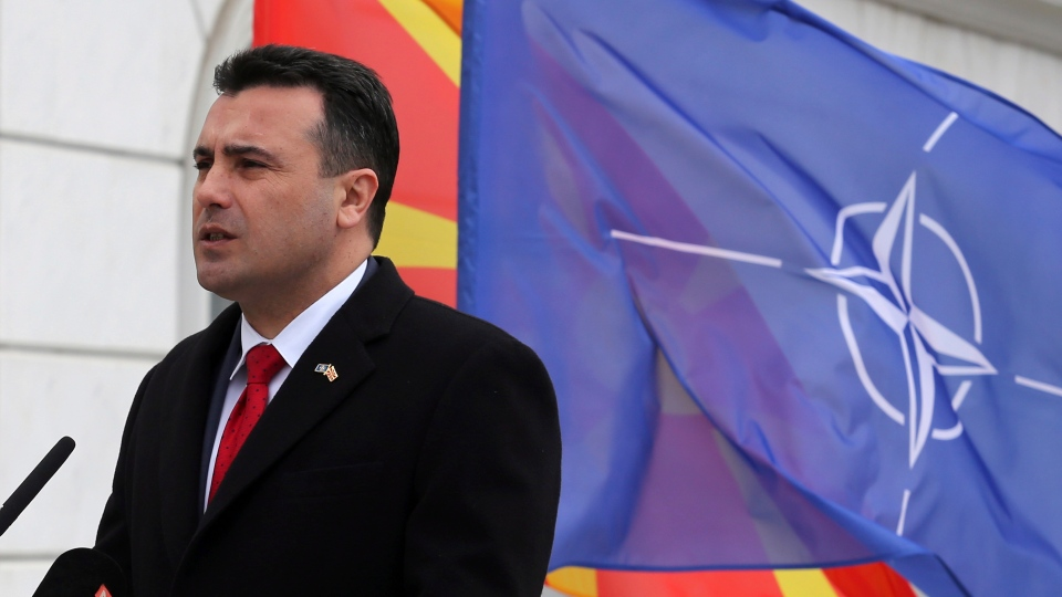 Macedonian Prime Minister Zoran Zaev delivers a speech in front of the NATO flag during a ceremony at the government building in Skopje, Tuesday, Feb. 12, 2019. (AP Photo/Dragan Perkovksi)