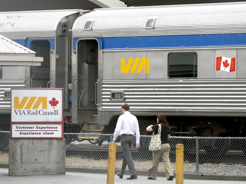 Via Rail employees walk past an idle train car in Vancouver, B.C., on Friday July 24, 2009. (Darryl Dyck / THE CANADIAN PRESS)
