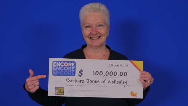 Barbara Jones posing with her $100,000 cheque