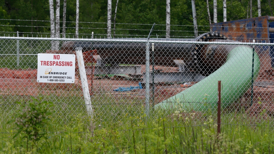 In this June 29, 2018 file photo, a No Trespassing sign is visible at a Enbridge Energy pipeline drilling pad along a rail line that traces the Minnesota-Wisconsin border south of Jay Cooke State Park in Minnesota. (AP Photo/Jim Mone)