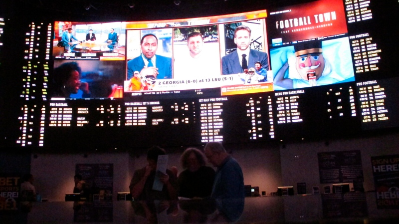 In this Oct. 12, 2018, file photo, people sit inside a sports betting lounge at the Ocean Resort Casino in Atlantic City N.J. (AP Photo/Wayne Parry, File)